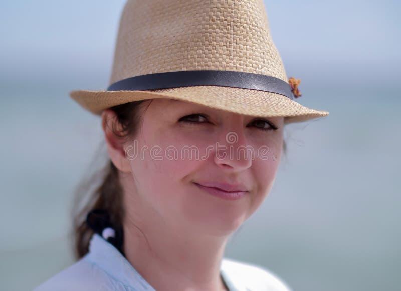 Portret młoda atrakcyjna kobieta patrzeje kamerę z kapeluszem zdjęcie royalty free
