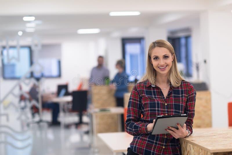 Portret młoda biznesowa kobieta przy biurem z drużyną w backgrou zdjęcia stock