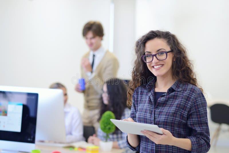 Portret młoda biznesowa kobieta przy nowożytnym początkowym biurowym wnętrzem, drużyna w spotkaniu w tle obrazy royalty free
