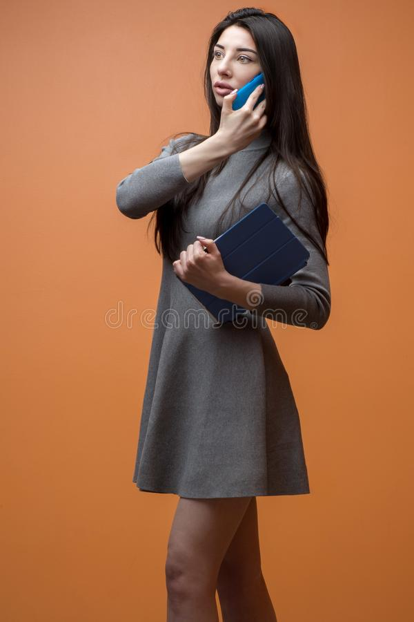 Portret młoda biznesowa kobieta w popielatej sukni z błękitnym smartphone i pastylką robi wezwaniu przeciw pomarańcze ścianie zdjęcia royalty free
