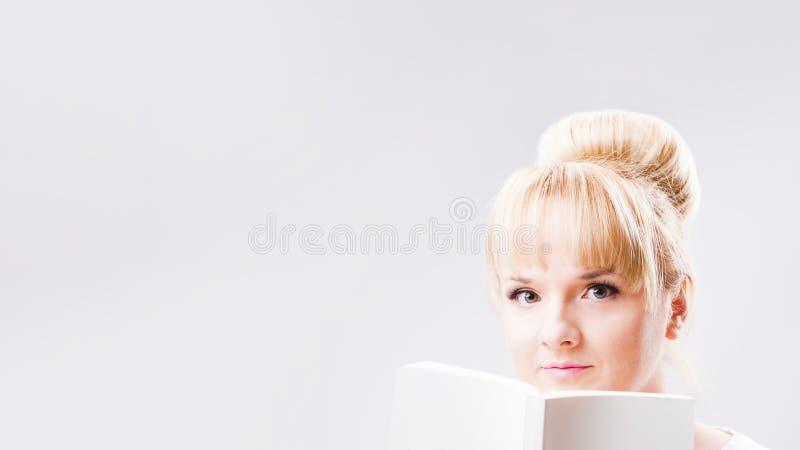 Portret młoda blond kobieta trzyma białą puste miejsce książkę na jasnopopielatym tle z babeczki fryzurą fotografia royalty free