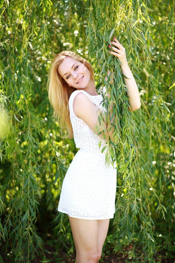 Portret młoda blond kobieta w zielonym wierzbowym drzewie fotografia royalty free