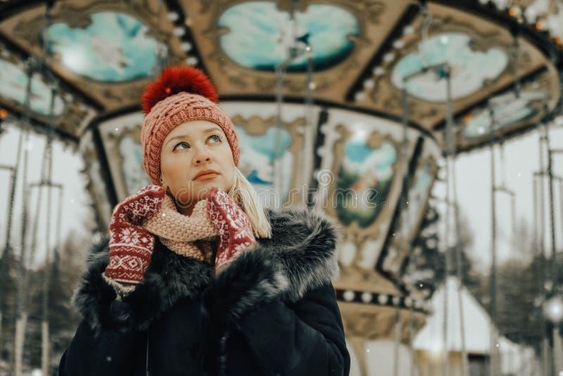 Portret młoda blond kobieta w zimie odziewa Czerwona nakrętka i mitynki Chodzić W parku zdjęcie stock