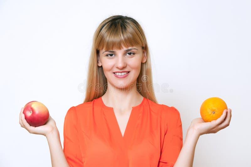 Portret młoda blond z włosami kobieta porównuje jabłka pomarańcze obraz royalty free