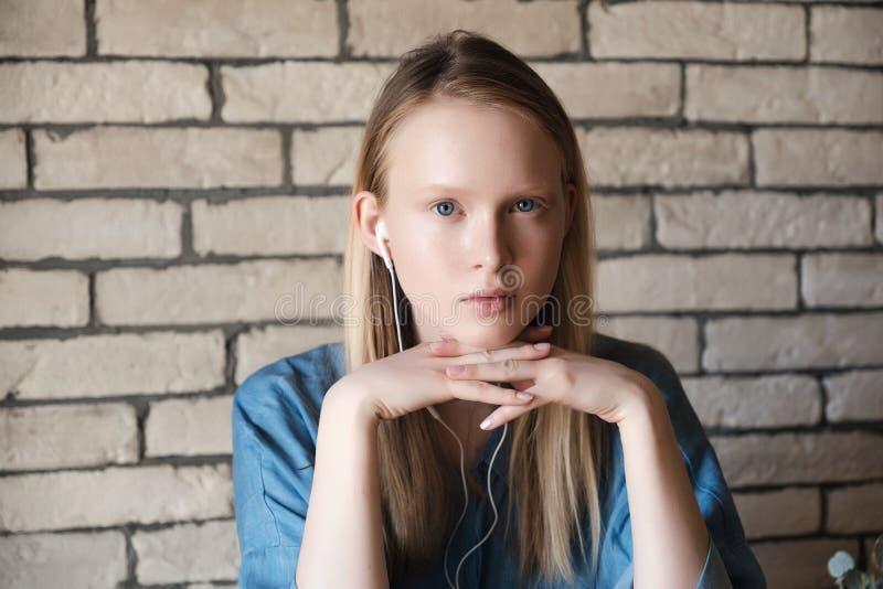 Portret młoda blondynki dziewczyna z hełmofonami Dziewczyny głowa odpoczywa na jej budka rękach zdjęcia stock