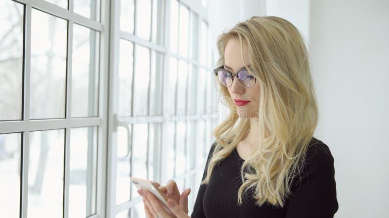 Portret młoda blondynki kobieta w szkłach z telefonem przy dużym okno fotografia stock