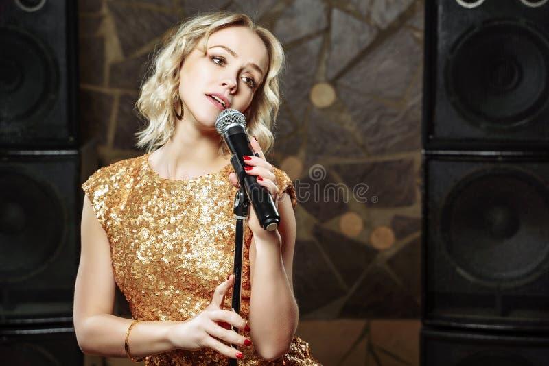 Portret młoda blondynki kobieta z mikrofonem na ciemnym tle fotografia royalty free