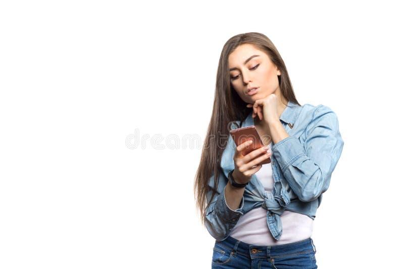 Portret młoda brunetki kobieta patrzeje smartphone w jej rękach z wahaniem i wistfulness, myśleć fotografia stock