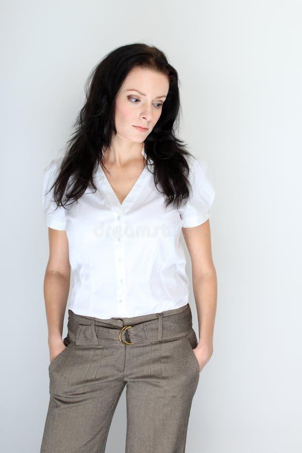 Portret młoda brunetki kobieta w formalnym kodzie ubioru z rękami w kieszeniach obrazy royalty free