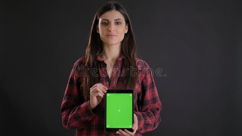Portret młoda długowłosa dziewczyna demonstruje pionowego zieleń ekran pastylka na czarnym tle w plaided koszula obraz royalty free