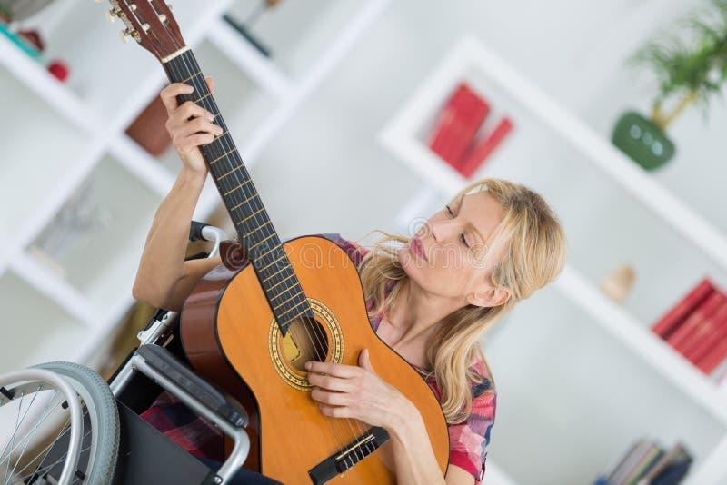Portret młoda dama w wózku inwalidzkim bawić się gitarę obrazy royalty free