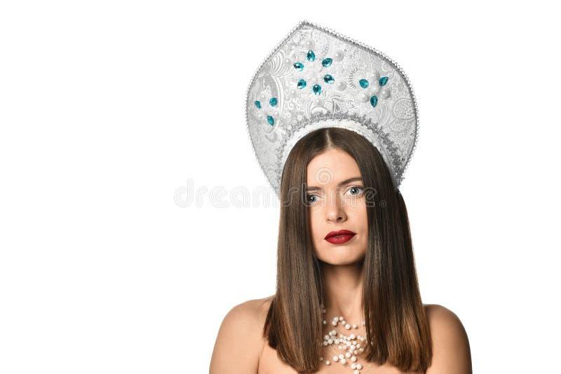 Portret młoda dziewczyna model w kokoshnik kapeluszu z naturalnym makeup i długim podmuchowym włosy odizolowywającymi patrzeć kam obrazy royalty free