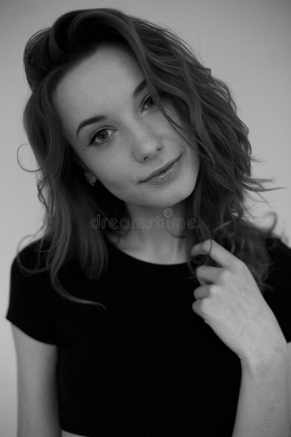 Portret młoda dziewczyna patrzeje kamerę w czarnej koszulce Czarny i biały pionowo fotografia fotografia stock