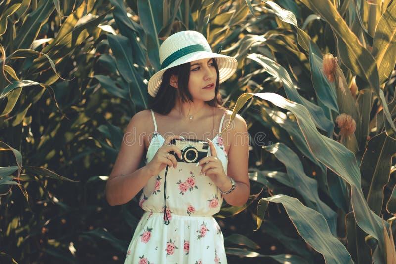 Portret młoda dziewczyna w kwiaciastej biel sukni, kapeluszu bierze fotografie z rocznik kamerą i obraz royalty free
