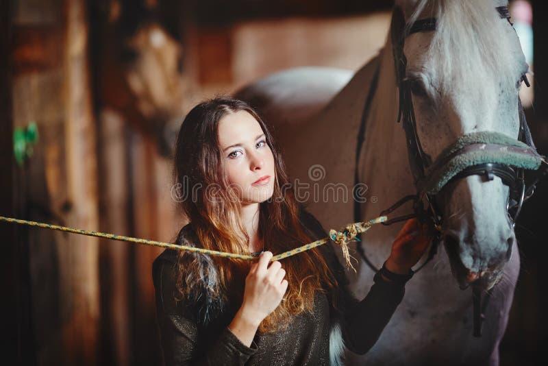 Portret młoda dziewczyna w wioski stajenkach z koniem Ubierający w ludu stylu obraz royalty free