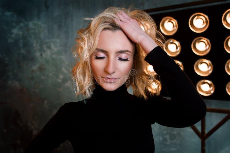 Portret młoda elegancka piękna atrakcyjna kędzierzawa dziewczyna w czarnym pulowerze na scenie zdjęcia stock