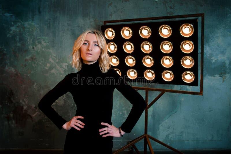 Portret młoda elegancka piękna atrakcyjna kędzierzawa dziewczyna w czarnym pulowerze na scenie zdjęcie royalty free