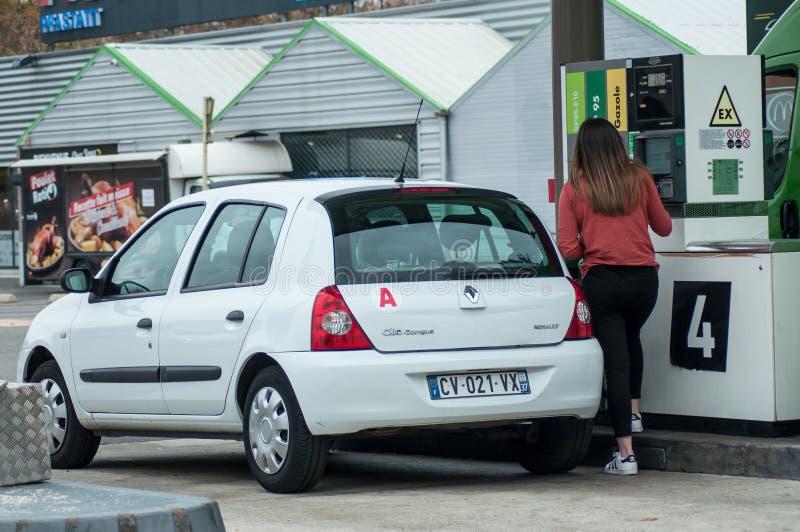 Portret młoda kierowca dziewczyna bierze paliwo w Intermarche benzynowej stacji zdjęcia stock