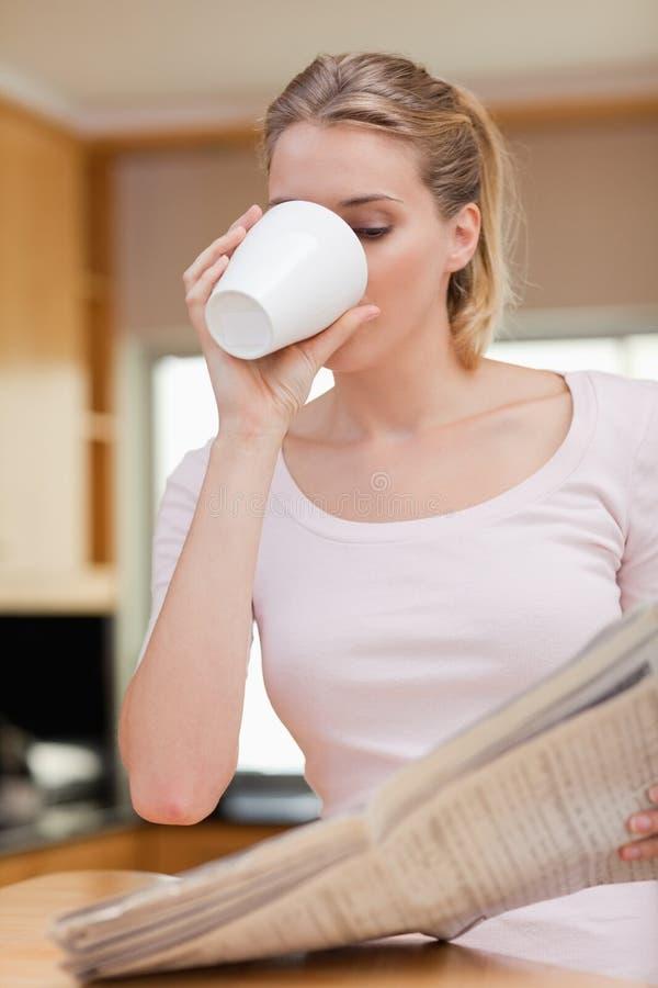 Portret młoda kobieta czyta wiadomość podczas gdy mieć herbaty zdjęcia royalty free