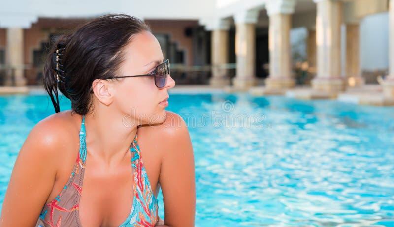 Portret młoda kobieta jest ubranym okulary przeciwsłonecznych relaksuje w swimm obrazy royalty free