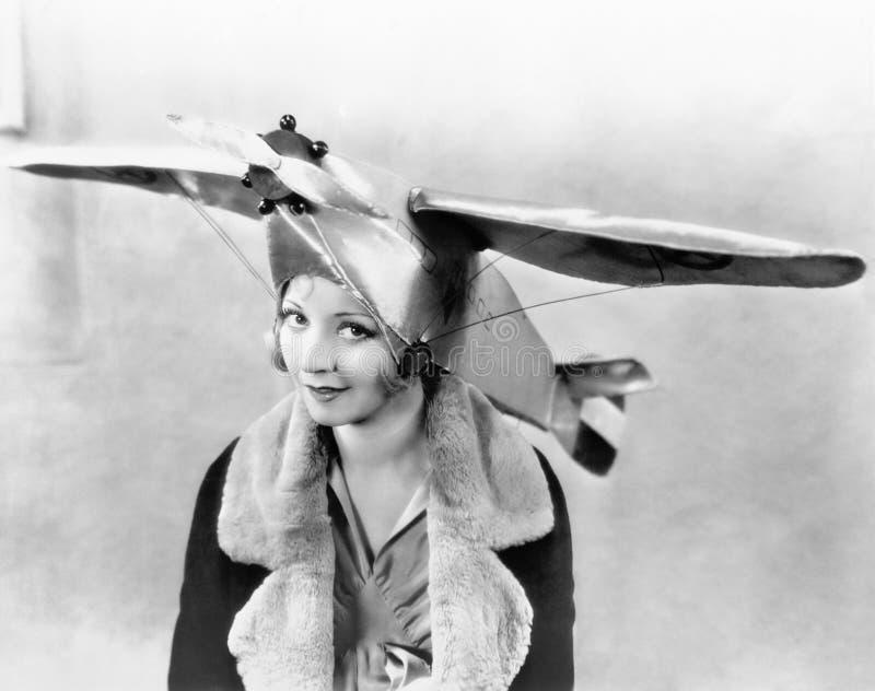 Portret młoda kobieta jest ubranym samolot kształtował nakrętkę (Wszystkie persons przedstawiający no są długiego utrzymania i ża zdjęcia stock