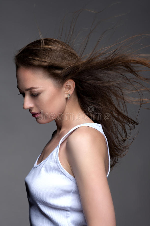 Portret młoda kobieta na szarym tle w białym zbiorniku t obraz royalty free