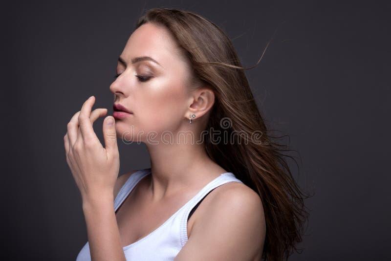 Portret młoda kobieta na szarym tle w białym zbiorniku t zdjęcia stock