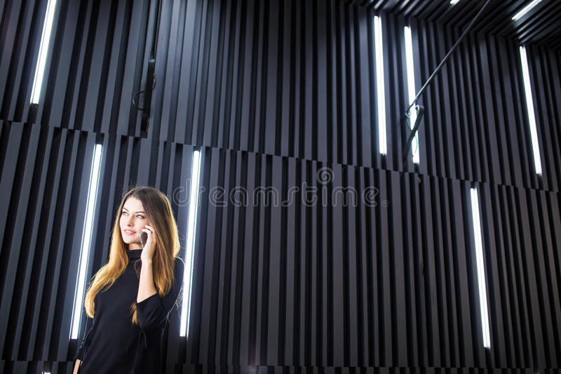 Portret młoda kobieta opowiada na telefonie komórkowym przeciw nowożytnej biuro ścianie obraz stock