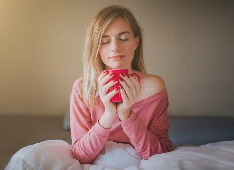 Portret młoda kobieta pije kawowego iin łóżko zdjęcia royalty free