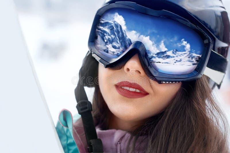 Portret młoda kobieta przy ośrodkiem narciarskim na tle góry i niebieskie niebo Pasmo górskie odbijający w masce narciarskiej zdjęcia royalty free