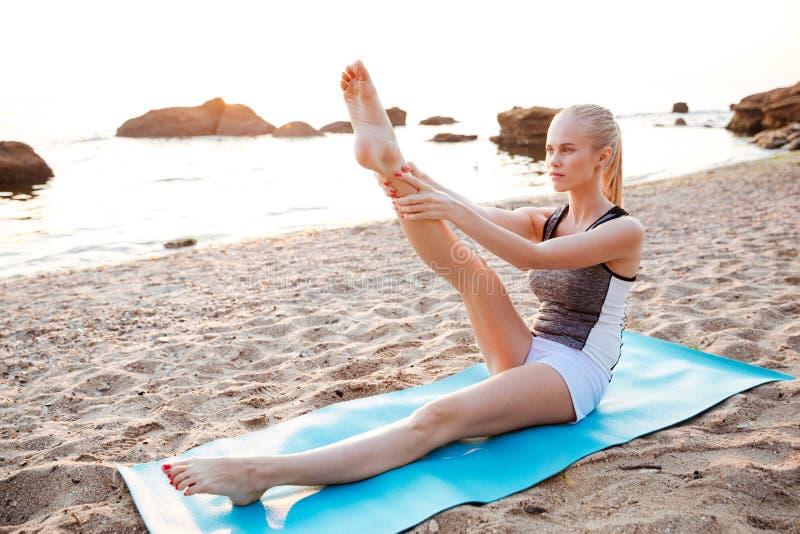 Portret młoda kobieta robi rozciąganie nóg ćwiczeniom outdoors zdjęcie royalty free