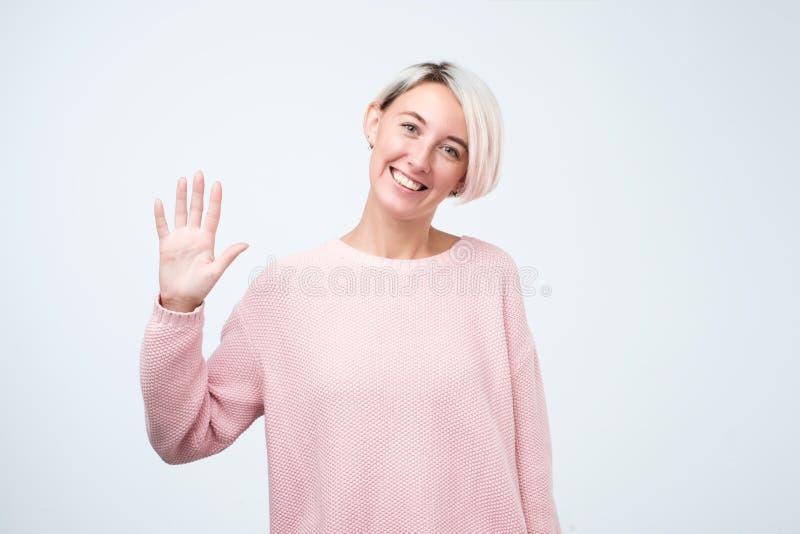 Portret młoda kobieta uśmiecha się cześć i mówi w różowym pulowerze obraz stock