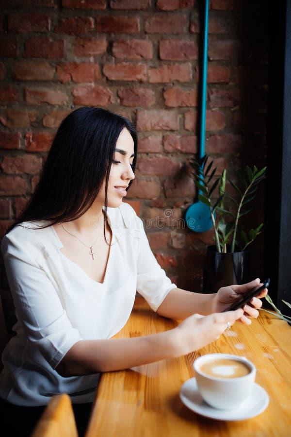 Portret młoda kobieta używa telefon komórkowego w wygodnym sklepie z kawą podczas gdy siedzący podczas pracy przerwy, powabny szc fotografia stock