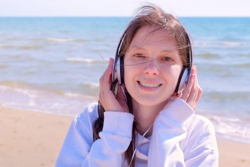 Portret młoda kobieta w hełmofonach cieszy się muzycznych spacery przy denną piasek plażą obrazy royalty free