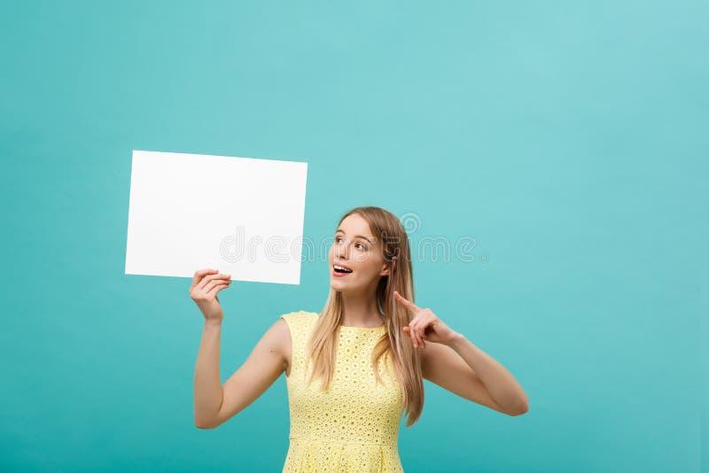 Portret młoda kobieta w koloru żółtego smokingowym wskazuje palcu przy boczną białą puste miejsce deską Odizolowywający nad błęki obraz royalty free