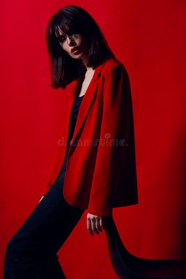 Portret młoda kobieta w profilu, pozuje w pracownianej pozycji na krześle w czerwonym kostiumu na czerwonym tle, fotografia royalty free
