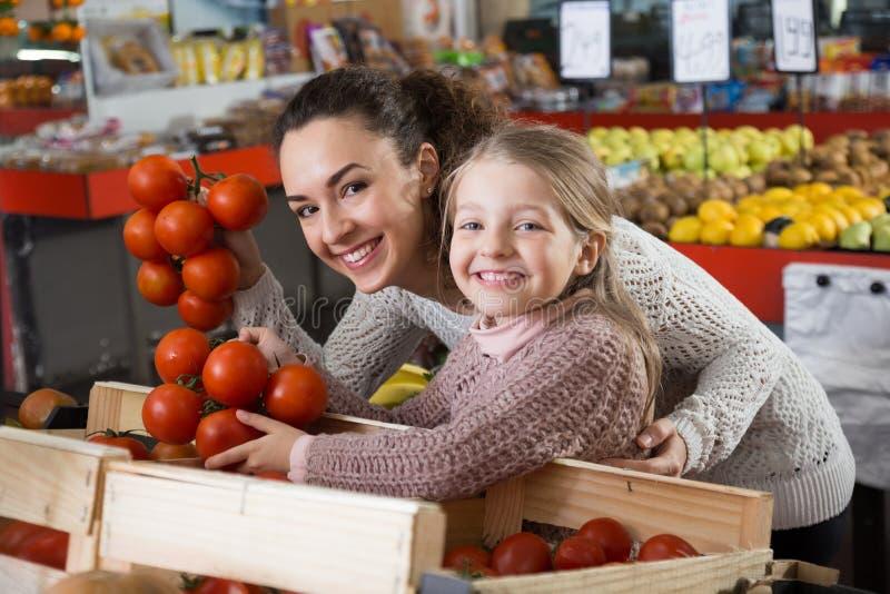 Portret młoda kobieta z piękną córką wybiera pomidory obraz royalty free