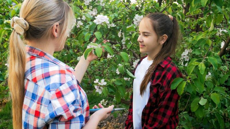 Portret młoda kobieta z teeange dziewczyną bierze opiekę drzewa w sadzie fotografia royalty free