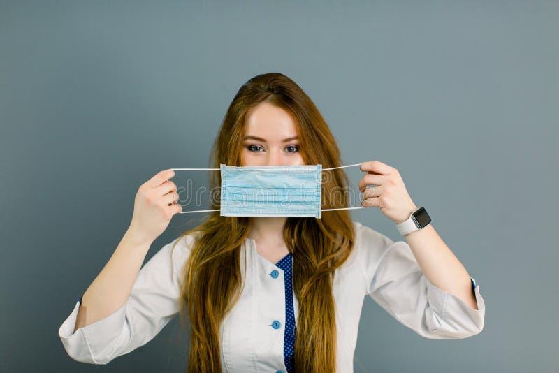 Portret młoda kobiety lekarka trzyma medyczną maskową patrzeje kamerę odizolowywająca na szarość fotografia royalty free