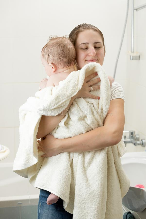 Portret młoda kochająca czułość macierzysta huggging jej dziecka po myć w skąpaniu obrazy royalty free