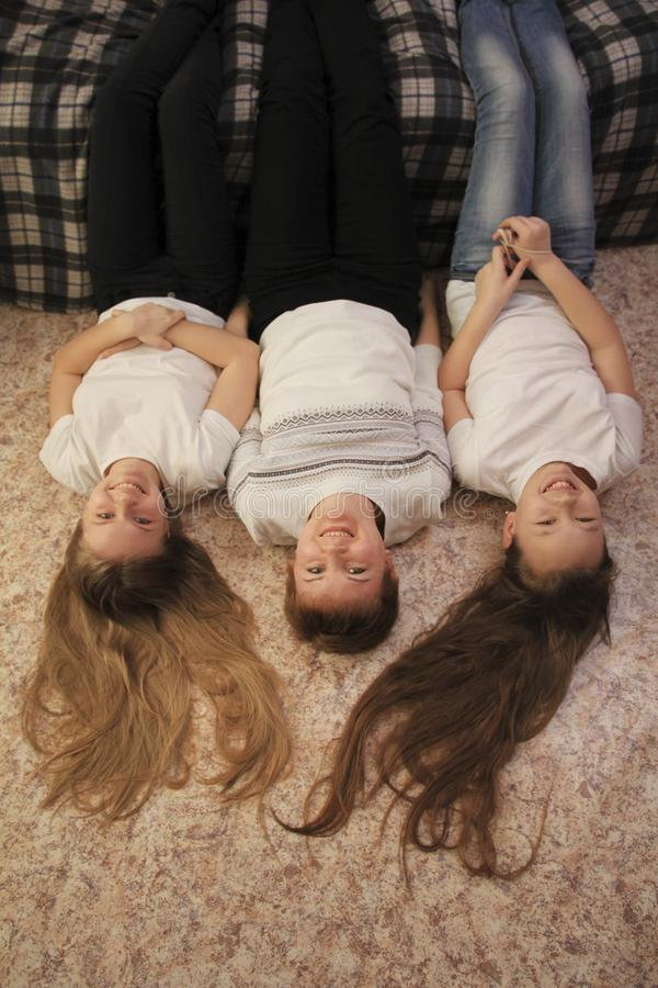 Portret młoda mama i jej dwa nastoletniej córki kłama na podłoga w domu, ich cieki na leżance zdjęcia royalty free