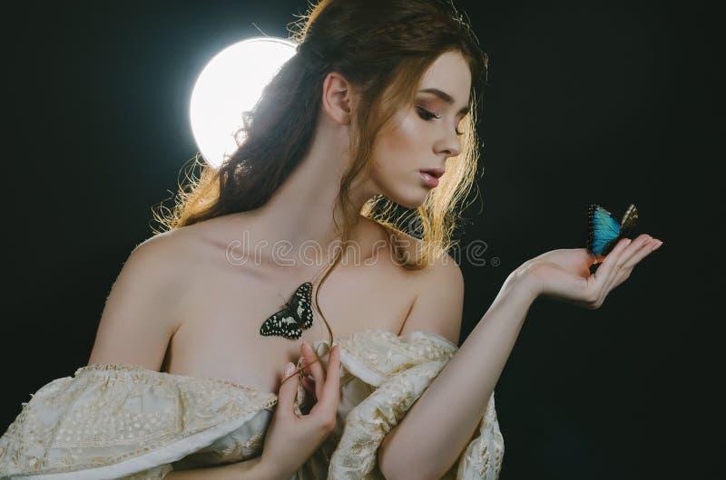Portret młoda miedzianowłosa kobieta w rocznika popiółu sukni z otwartym i ramiona w blasku księżyca na czarnym tle z powrotem S fotografia royalty free