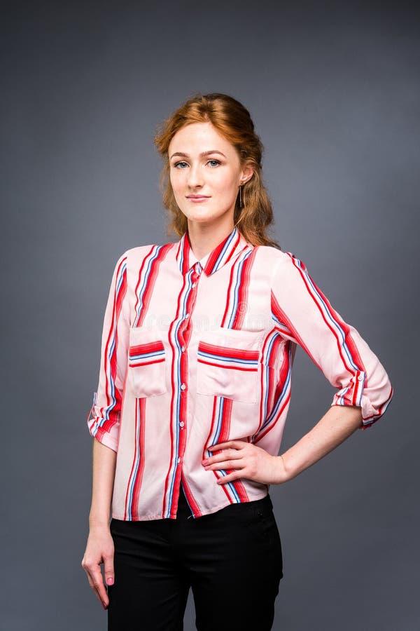 Portret młoda miedzianowłosa piękna dziewczyna w studiu na szarym odosobnionym tle Kobiety uśmiechy w czerwonym shir i stojaki obrazy royalty free