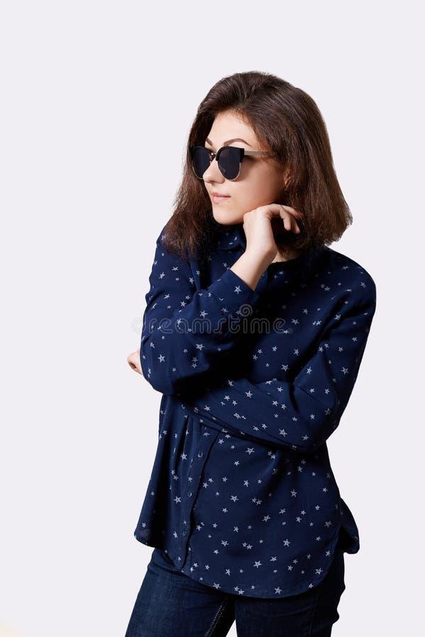 Portret młoda modniś dziewczyna trzyma jej rękę pod podbródkiem patrzeje poważnie ubierał w eleganckiej koszula i cajgów round ok fotografia royalty free