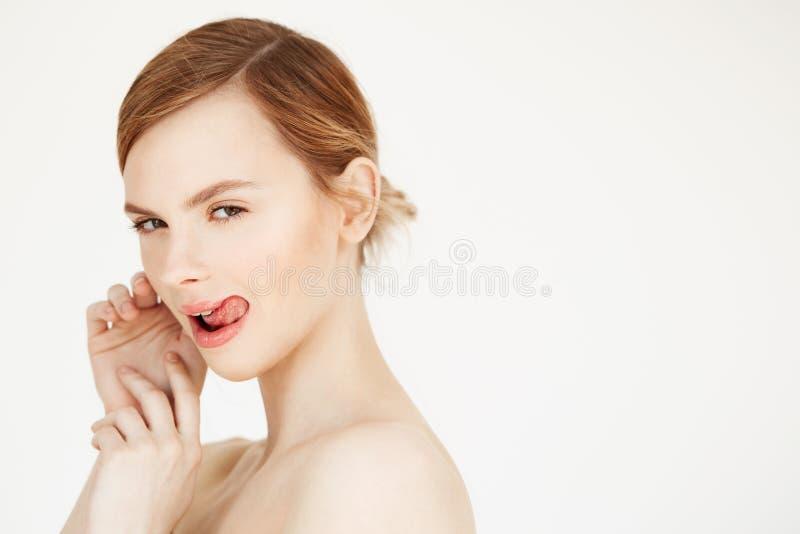 Portret młoda naga piękna dziewczyna patrzeje kamerę nad białym tłem z naturalnym uzupełniał pokazywać jęzor zdjęcie stock