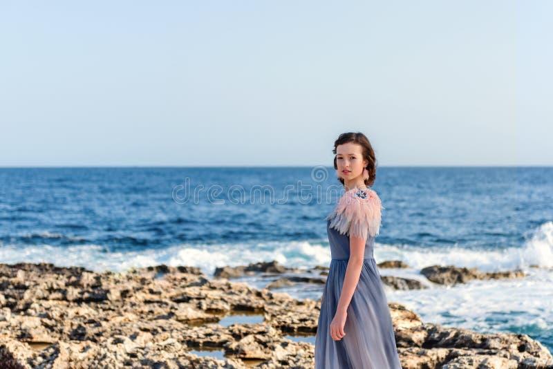 Portret młoda nikła pełen wdzięku dziewczyna w szarej sukni z menchiami upierza z rozszalałym jaskrawym błękitnym morzem na tle zdjęcie stock