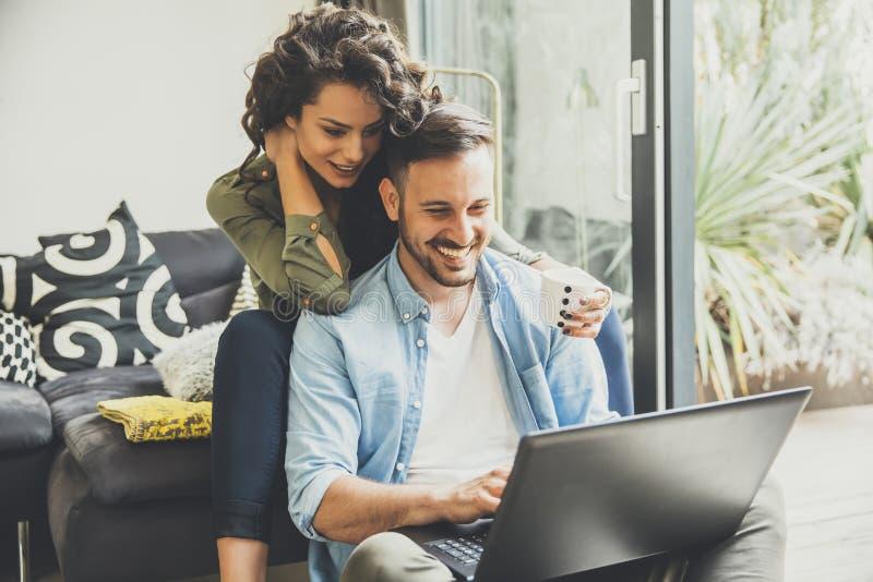 Portret młoda para używa laptop salowego w domu zdjęcia stock