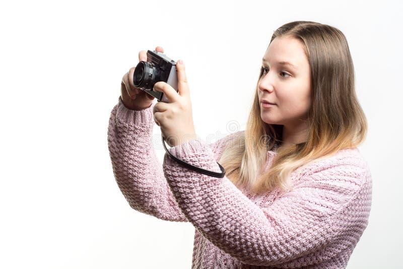 Portret młoda piękna blondynki dziewczyna jest ubranym jasnoróżowego trykotowego pulower patrzeje rocznik kamerę w ona ręki zdjęcie royalty free