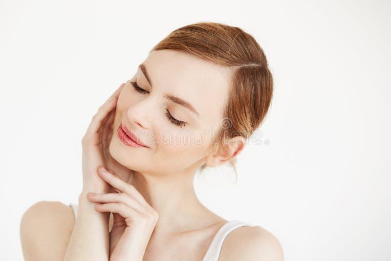 Portret młoda piękna dziewczyna ono uśmiecha się z zamkniętymi oczami dotyka twarz nad białym tłem Twarzowy traktowanie piękno zdjęcia royalty free