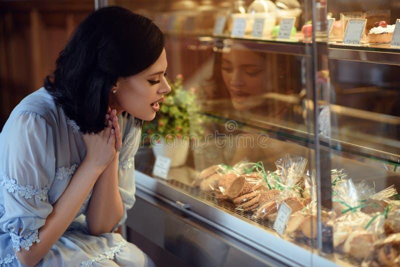 Portret młoda piękna dziewczyna patrzeje gablotę wystawową z tortami i ciastkami z podnieceniem na jej twarzy obrazy royalty free